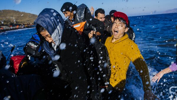 Refugees and migrants react as they arrive on a rubber boat on the Greek island of Lesbos, after crossing the Aegean sea from Turkey, on October 15, 2015. - Sputnik International