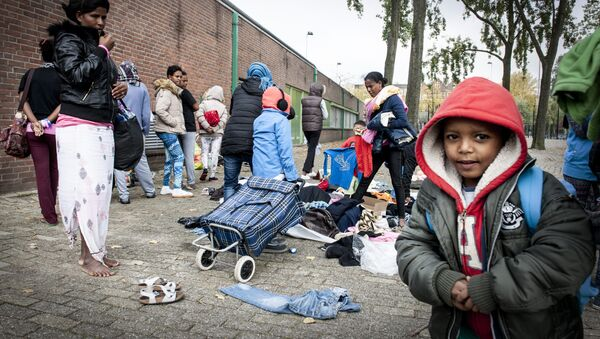 Refugees collect clothes, brought by residents of the neighborhood, outside the Schuttersveld Sports Centre designed as emergency shelter in Rotterdam, The Netherlands, on October 9, 2015 - Sputnik International