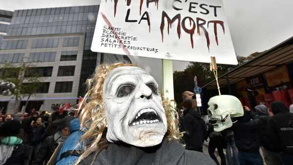 A protester with a mask demonstrates against the free trade agreement TTIP (Transatlantic Trade and Investment Partnership) during an EU summit in Brussels, Belgium on Thursday, Oct. 15, 2015. - Sputnik International