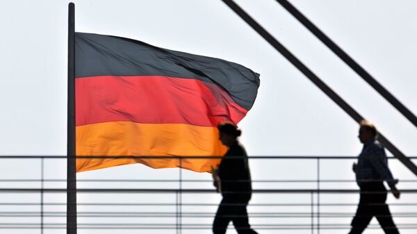 People pass a giant German National flag on the Reichstag, which houses the German parliament Bundestag, as they cross a bridge between two office buildings on Thursday, April 2, 2009 in Berlin - Sputnik International