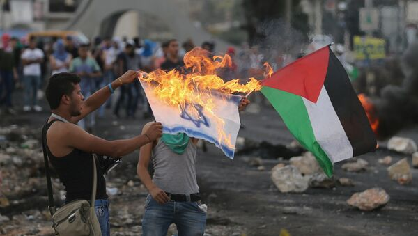 A protester burns a replica Israeli flag as another holds a Palestinian flag during clashes with the Israeli troops near the Jewish settlement of Bet El, near the West Bank city of Ramallah, 18 October 2015 - Sputnik International