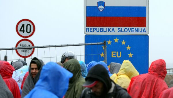 Migrants and refugees wait in the rain as they wait to enter Slovenia, at the Croatian-Slovenian border in Trnovec, on October 19, 2015. - Sputnik International
