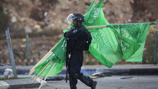 A member of the Israeli security forces carries flags of the Palestinian movement Hamas. - Sputnik International