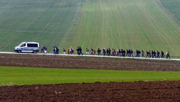 Migrants are escorted by German police to a registration centre, after crossing the Austrian-German border in Wegscheid near Passau, Germany, October 20, 2015 - Sputnik International