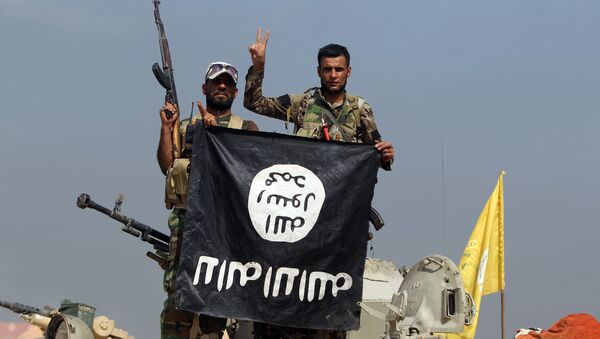 Iraqi Shiite fighters from the Popular Mobilisation units, fighting alongside Iraqi government forces, display, upside down, the flag of the Islamic State (IS) group during a military operation aimed at the centre of Baiji, some 200 kilometres north of Baghdad on October 19, 2015 - Sputnik International