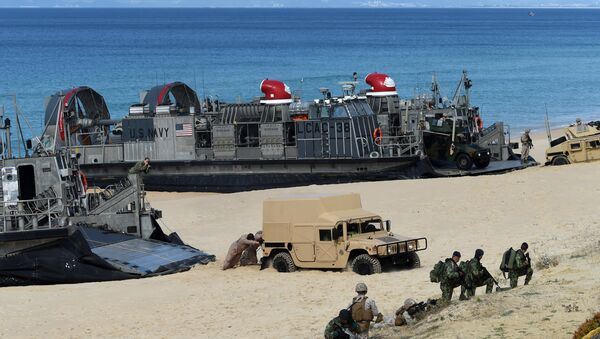 US marines push a Humvee stuck on the sand as they disembark from the overcrafts deployed by the USS Arlington amphibious transport dock during the NATO's Trident Juncture exercise at Pinheiro da Cruz beach, south of Lisbon, near Grandola on October 20, 2015 - Sputnik International