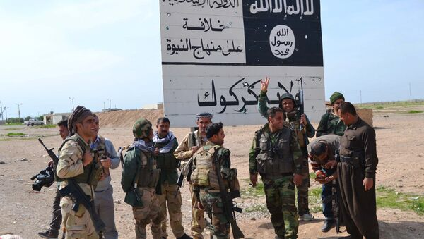 Iraqi Kurdish Peshmerga fighters stand next to an Islamic State (IS) group sign at the entrance to the northern Iraqi town of Hawija, south of Kirkuk on March 9, 2015 after they reportedly re-took the area from IS jihadists - Sputnik International
