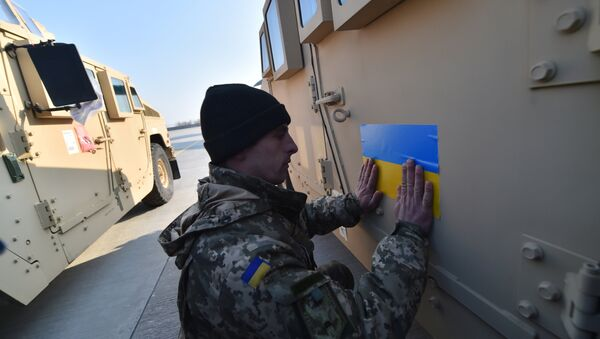 An Ukrainian serviceman sticks an Ukrainian flag on a Humvee at Kiev airport on March 25, 2015 during a welcoming ceremony of the first US plane delivery of non-lethal aid, including 10 Humvee vehicles - Sputnik International