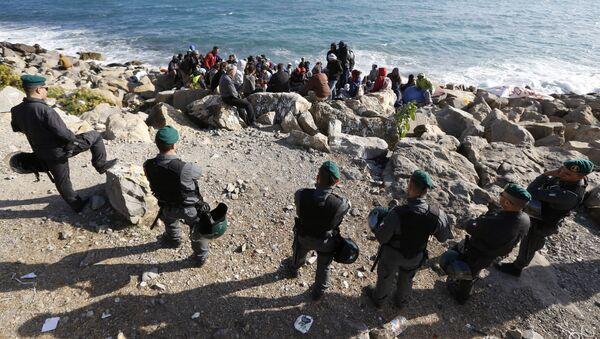 Migrants wait on the rocks on the shoreline under the surveillance of policemen on September 30, 2015 at the French-Italian border in Ventimiglia - Sputnik International