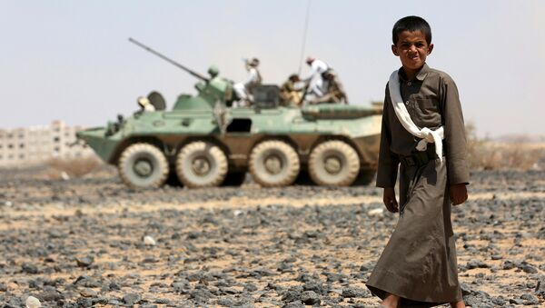 A boy walks in front of fighters of the Popular Resistance Committees riding on an armored vehicle during a ceremony where they formally take over territory that the government had managed to recover from Houthi militants, in the central province of Marib October 11, 2015. - Sputnik International