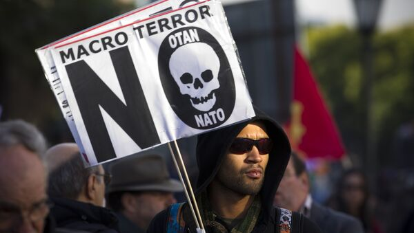 A protester holds a sign that reads Macro terror, no to NATO during a demonstration against NATO in Lisbon, on Saturday, Nov. 20, 2010 - Sputnik International