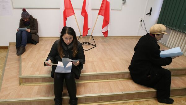 Voters read documents during the first round of Polish local elections in Warsaw, Poland, Sunday, Nov. 16, 2014 - Sputnik International