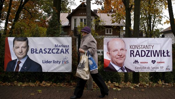 A woman walks in front of the election posters of Law and Justice candidates Mariusz Blaszczak (L) and Konstanty Radziwill (R) in Milanowek, outskirts of Warsaw, Poland October 23, 2015. - Sputnik International