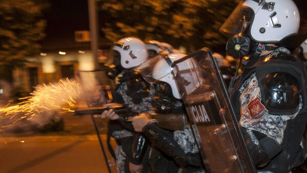 A riot policeman fires tear gas at protesters in front of the parliament building in Podgorica, Montenegro, October 24, 2015. - Sputnik International