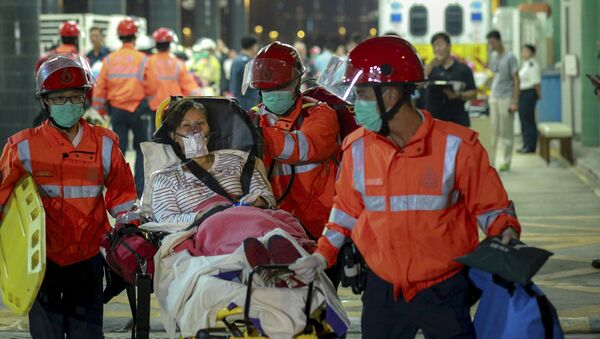 An injured ferry passenger is escorted by rescuers after getting onshore in Hong Kong, China October 25, 2015. - Sputnik International