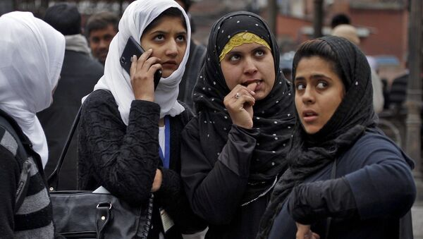 Kashmiri girls stand on a road divider after vacating their office buildings following an earthquake in Srinagar October 26, 2015.  - Sputnik International