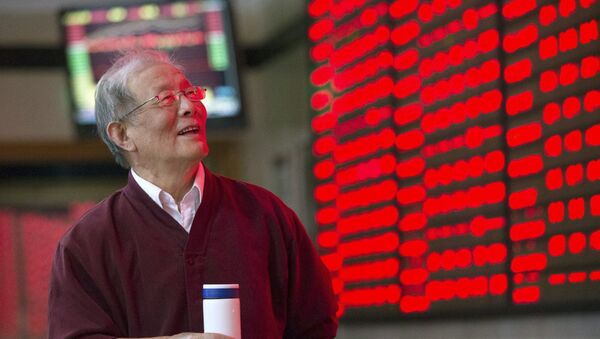 An investor looks at an electronic board showing stock information at a brokerage house in Nanjing, Jiangsu province, China, October 12, 2015. - Sputnik International