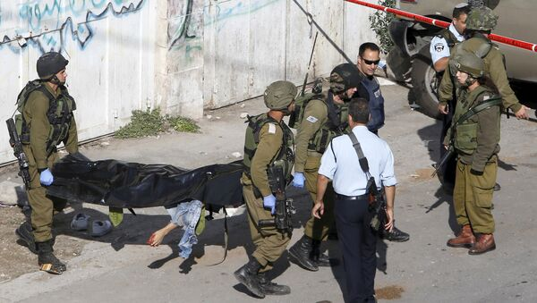 Israeli soldiers carry the body of a Palestinian, who Israeli police and army said stabbed a soldier, after he was shot by an Israeli policeman, in the West Bank old city of Hebron October 29, 2015 - Sputnik International
