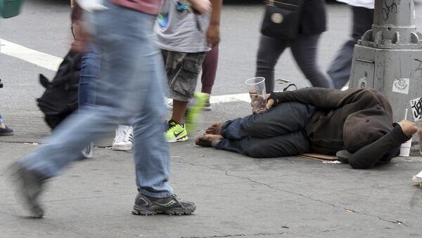 People walk past a homeless man asking for money on 14th Street, Friday, Sept. 4, 2015, in New York - Sputnik International