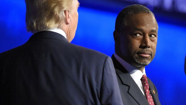 Ben Carson watches as Donald Trump takes the stage during the CNBC Republican presidential debate at the University of Colorado. - Sputnik International