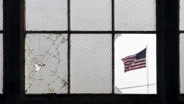 In this 2009 file photo, reviewed by the U.S. military, an American flag fluttering in the wind is pictured through a broken window from inside an airplane hangar used for media activities at Camp Justice, the site of the U.S. war crimes tribunal compound, at Guantanamo Bay U.S. Naval Base, Cuba, July 16, 2009 - Sputnik International