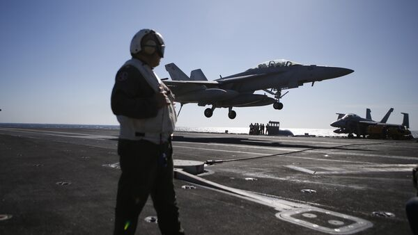 A US Navy crew member looks at an F/A-18 Super Hornet fighter landing onto the deck of the USS Ronald Reagan, a Nimitz-class nuclear-powered aircraft carrier, during a joint naval drill between South Korea and the US in the West Sea off South Korea on October 28, 2015 - Sputnik International