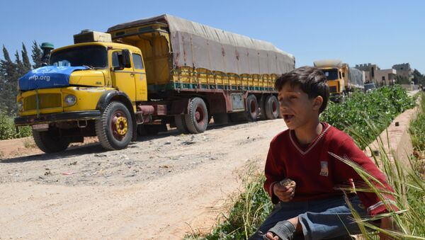 A Syrian child eats as he sits near a convoy of trucks from the World Food Programme and UNICEF carrying international aid as they drive in the countryside of the Homs district en route to the rebel held area of Al-Rastan north of the central Syrian city of Homs, on April 21, 2015. - Sputnik International