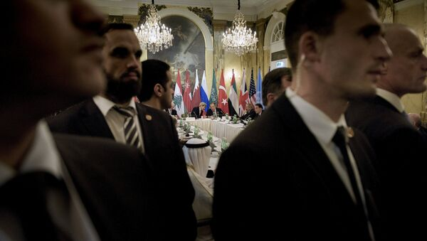Security staff stand as US Secretary of State John Kerry (back L) and Russian Foreign Minister Sergei Lavrov (back 2nd L) chat before a meeting with 17 nations, the European Union and United Nations at the Hotel Imperial in Vienna, October 30, 2015 - Sputnik International