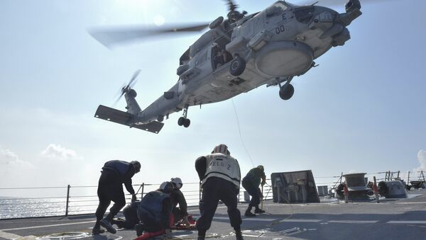 U.S. Navy Sailors participate in a medical training exercise on the deck of the Arleigh Burke-class guided missile destroyer USS Lassen (DDG 82) with an MH-60R Seahawk helicopter, in the South China Sea, October 28, 2015 - Sputnik International