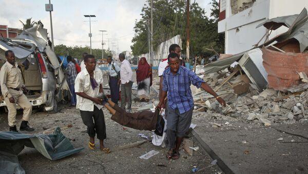 Somali men carry a wounded person to an ambulance outside the Sahafi Hotel in Mogadishu, Somalia Sunday, Nov. 1, 2015 - Sputnik International