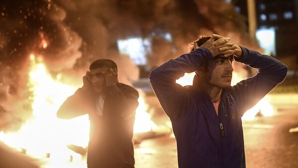 People react as smoke billows from burning pallets set on fire during clashes between Turkish riot policemen and Kurdish protesters in the southeastern city of Diyarbakir on November 1, 2015 after first results of the Turkish general election showed a clear victory to the Justice and Development Party (AKP). Turkish police fired tear gas and water cannon at Kurds who were protesting after the election appeared to deliver a clear victory to AKP, an AFP photographer said. Latest results say the pro-Kurdish People's Democratic Party (HDP) won slightly over 10 percent of the vote, just enough to scrape into parliament. - Sputnik International
