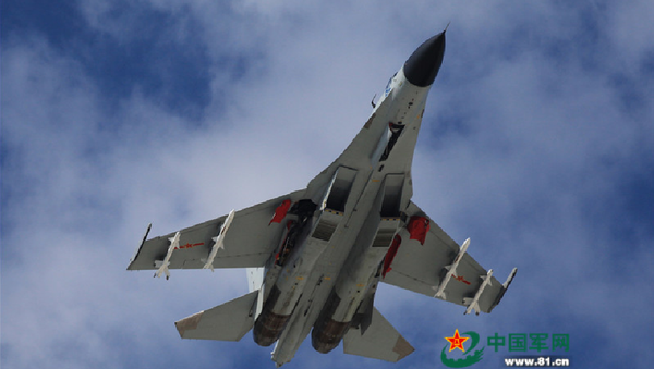 A J-11 fighter flies above the South China Sea on Oct. 30, 2015. An aviation division under the South China Sea Fleet of the Chinese PLA Navy carried out on Friday training on real air battle tactics. - Sputnik International