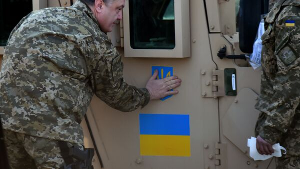 Ukrainian President Petro Poroshenko sticks an Ukrainian flag and the state emblem on an armoured vehicle at Kiev airport on March 25, 2015 during a welcoming ceremony of the first US plane delivery of non-lethal aid, including 10 Humvee vehicles - Sputnik International