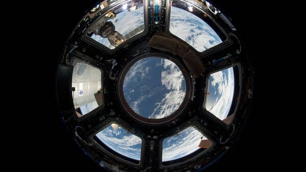 A view of Earth as seen from the Cupola on the Earth-facing side of the International Space Station. Visible in the top left foreground is a Russian Soyuz crew capsule. In the lower right corner, a solar array panel can be seen. - Sputnik International