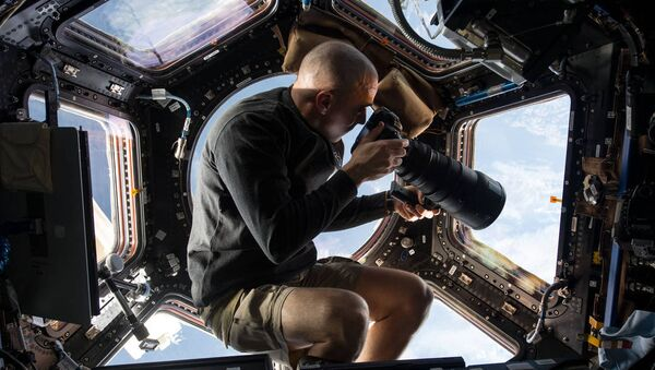Inside the Cupola, NASA astronaut Chris Cassidy, an Expedition 36 flight engineer, uses a 400mm lens on a digital still camera to photograph a target of opportunity on Earth some 250 miles below him and the International Space Station. Cassidy has been aboard the orbital outpost since late March and will continue his stay into September. - Sputnik International