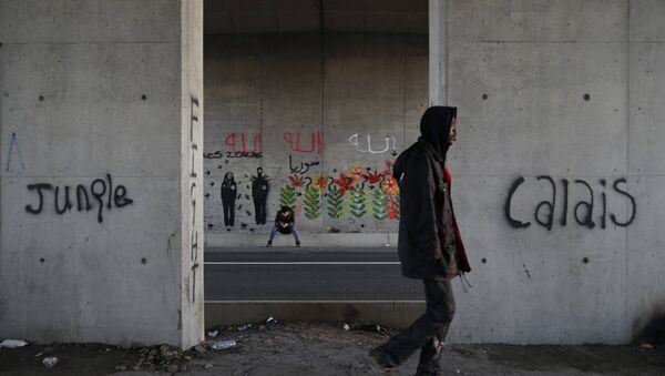 Migrants make their way along a road near graffiti with the words Jungle, Calais in Calais, France, October 20, 2015. - Sputnik International