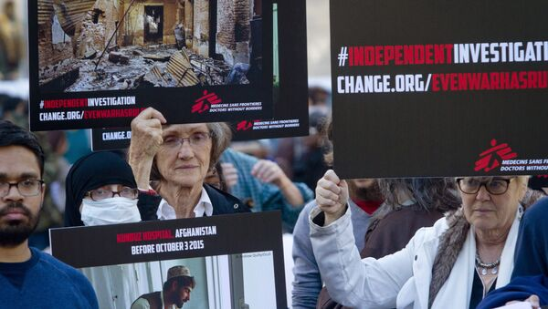 Supporters of Doctors Without Borders hold before and after images during a rally to mark the one-month anniversary of a U.S. military strike on its trauma center in Afghanistan. - Sputnik International