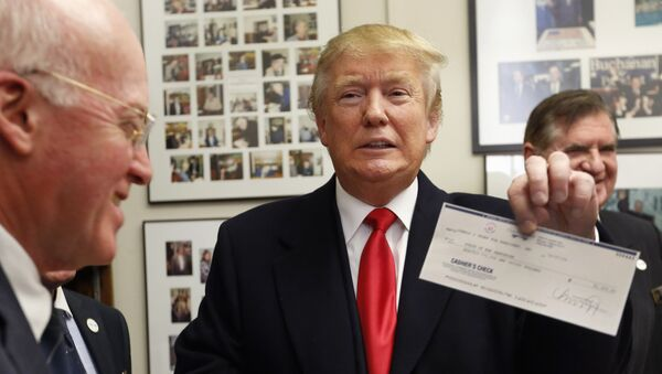 Secretary of State Bill Gardner watches at left as Republican presidential candidate Donald Trump shows off his filling fee check after filing papers to be on the nation's earliest presidential primary ballot. - Sputnik International