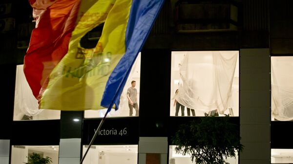 People re-decorate a shop as Romanians waving a flag fill the Calea Victoriei, a main avenue of the Romanian capital, during a large protest in Bucharest, Romania, Tuesday, Nov. 3, 2015.  - Sputnik International