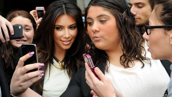 In this Friday, Sept. 21, 2012 file photo Kim Kardashian, left, is surrounded by her fans who are attempting to have their photographs taken with her as she leaves a radio station in Melbourne, Australia. - Sputnik International