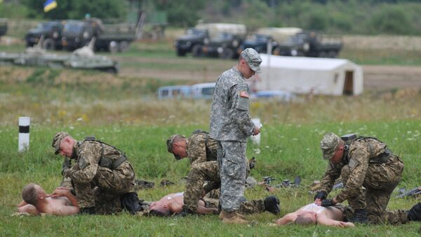 US serviceman teaches Ukrainian soldiers how to give emergency medical aid during the Rapid Trident/Saber Guardian 2015 military exercises at the International Peacekeeping and Security Centre base outside Lviv, Ukraine, Friday, July 24, 2015 - Sputnik International