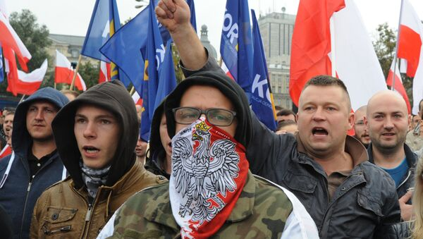 Protesters shout anti migrant slogans as several thousand right wing nationalists march through downtown, demonstrating against EU proposed quotas for Poland to spread the human tide of refugees around Europe, in Warsaw, Poland, Saturday, Sept. 12, 2015 - Sputnik International