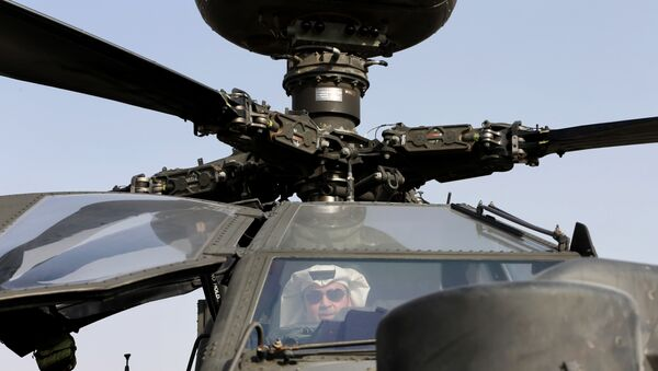 An Emirati man checks out an Apache helicopter during the opening of the Dubai Airshow in United Arab Emirates, Sunday, Nov. 8, 2015 - Sputnik International