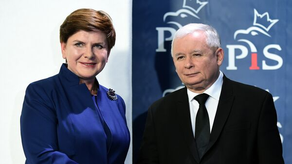 Jaroslaw Kaczynski (R), the leader of the conservative Law and Justice (PiS) party, shakes hands with designated prime minister Beata Szydlo after she announced members of her new cabinet on November 9, 2015 in Warsaw - Sputnik International
