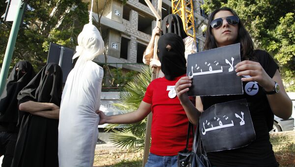 Activists from a civil organization reenact an execution scene in front of the Saudi Arabia Embassy in Beirut, Lebanon, Thursday, April 1, 2010, as they protest a possible beheading of a Lebanese man accused of witchcraft in Saudi Arabia. The lawyer of Lebanese TV psychic Ali Sibat who was convicted in Saudi Arabia for witchcraft said Thursday her client could be beheaded this week and urged Lebanese and Saudi leaders to help spare his life. The Arabic writing on banners read:don't kill. - Sputnik International