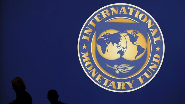 Visitors are silhouetted against the logo of the International Monetary Fund at the main venue for the IMF and World Bank annual meeting in Tokyo in this October 10, 2012 file photo. - Sputnik International