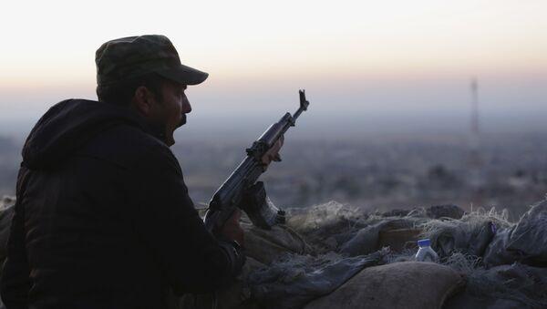 A Kurdish fighter, known as a peshmerga, yawns as he stands guard on the frontline in Sinjar, Iraq, Friday, Nov. 13, 2015. - Sputnik International