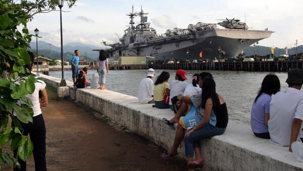 People stand near the docked amphibious assault ship USS Essex at Subic Bay, Philippines. - Sputnik International