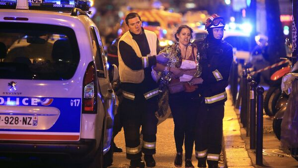 Rescue workers help a woman after a shooting, outside the Bataclan theater in Paris, Friday Nov. 13, 2015. - Sputnik International