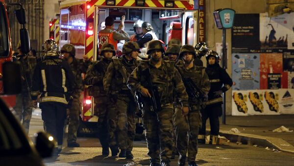 Soldiers walk in front of an ambulance as rescue workers evacuate victims near La Belle Equipe, rue de Charonne, at the site of an attack on Paris on November 14, 2015 - Sputnik International